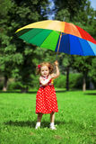 Little girl with a rainbow umbrella in park Stock Photo
