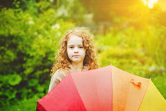 Little girl with rainbow umbrella, under sunshine. Royalty Free Stock Photos