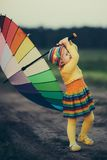 Little girl with rainbow umrella in the field Royalty Free Stock Photography