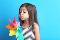 Little girl with rainbow whirligig. Beautiful little girl with rainbow whirligig on blue background Stock Photo