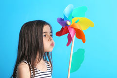 Little girl with rainbow whirligig. Beautiful little girl with rainbow whirligig on blue background Royalty Free Stock Photos