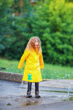Little girl in raincoat and boots playing in the rain outdoors Royalty Free Stock Photography
