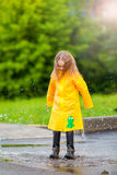 Little girl in raincoat and boots playing in the rain outdoors Stock Photography