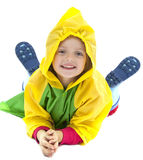 Little girl with raincoat playing on the ground. Little girl with raincoat and rubber boots on white background Royalty Free Stock Image