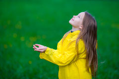 Little girl in raincoat playing in the rain outdoors Royalty Free Stock Photography