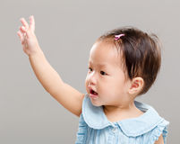 Little girl raise her hand up. With gray background Royalty Free Stock Photography