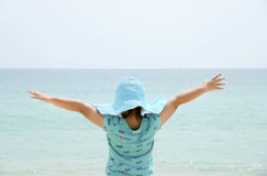 Little girl with raised arms near the sea. Stock Image