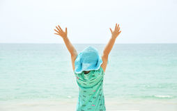 Little girl with raised arms near the sea. Stock Photos