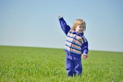 Little girl with raised hand in a field Stock Image