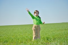 Little girl with raised hand in a field Stock Photos