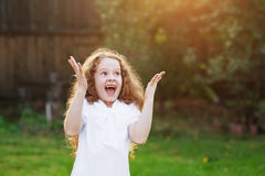 Little girl raised her hands up in surprise or dreaming. Royalty Free Stock Photo
