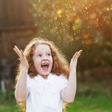 Little girl raised her hands up in surprise or dreaming. Royalty Free Stock Image