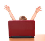 Little girl raised his hands behind laptop Stock Photos