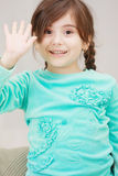 Little girl raises hand in greeting Royalty Free Stock Photo