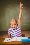 Little girl raising hand in classroom Royalty Free Stock Image