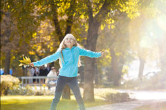Little Girl Raising her Arms and Enjoying Sunny Autumn Day stock photography