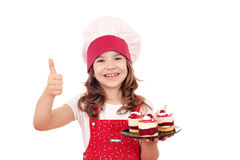 Little girl with raspberry cake and thumb up Royalty Free Stock Photography