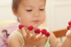 Little girl with raspberry on fingers Stock Images