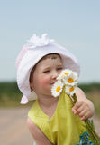 Little girl reaches out  camomiles Stock Images