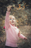 Little girl reaches for a tree branch Royalty Free Stock Photography