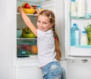 Little girl reaching apples in fridge Stock Images