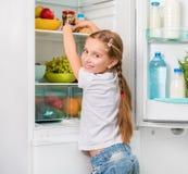 Little girl reaching a jar of mushrooms Stock Photos