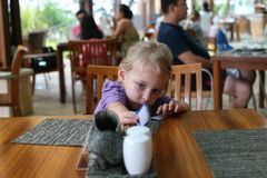 Little girl reaching for a napkin at the table Stock Photography