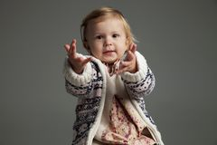 Little girl reaching out. With her hands on grey background Stock Photography