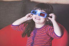 Kids and technology concept. Little girl reacts while watching a movie with 3D glasses Royalty Free Stock Images