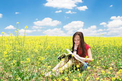 Little girl read book in nature. Little girl read book in flower garden stock photo