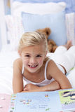 Little girl reading in bed Stock Image
