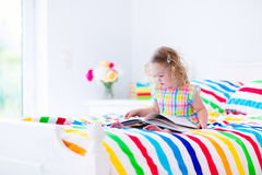 Little girl reading in bed Stock Images