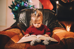 Little girl reading a bedtime story by the fireplace. Pre-christmas mood. New Years is soon stock images