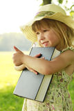 Little girl reading the Bible in nature Stock Photos