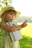 Little girl reading the Bible in nature Stock Photo