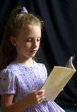 Little Girl Reading a book. A young girl in a purple dress reads a book at home in Holly Hill, Florida Stock Photo