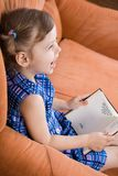 Little girl reading book. And have fun Stock Images