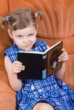 Little girl reading book. And smirk Royalty Free Stock Image
