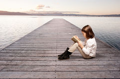 Little girl reading a book. On a wharf Royalty Free Stock Images