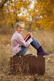 Little girl is reading a book in autumn. Wood Stock Image