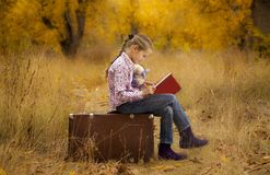Little girl is reading a book in autumn