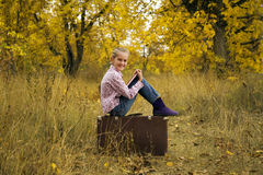 Little girl is reading a book in autumn. Wood Stock Photography
