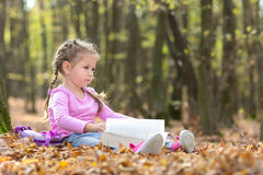 Little girl is reading a book Stock Photos