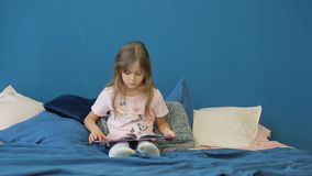 A little girl is reading a book on the bed. stock footage
