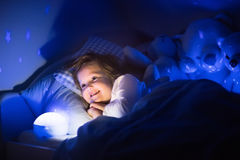 Little girl reading a book in bed Stock Photos