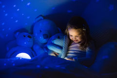 Little girl reading a book in bed Royalty Free Stock Images
