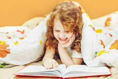 Little girl reading a book in bed before going to sleep. Toned i Royalty Free Stock Photo