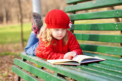 Little girl reading book on a bench Stock Images