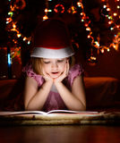 Little girl reading a book beside  Christmas tree Royalty Free Stock Images