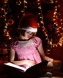 Little girl reading a book beside  Christmas tree Royalty Free Stock Image